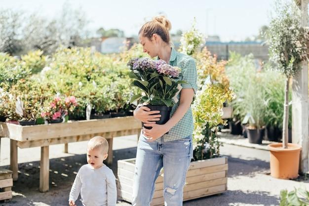 Mutter mit sohn kauft lila hortensie in einem topf in einem blumenladen