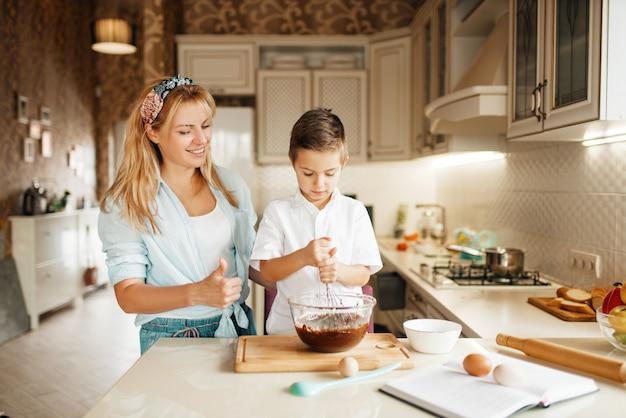 Mutter mit sohn mischen geschmolzene schokolade in einer schüssel