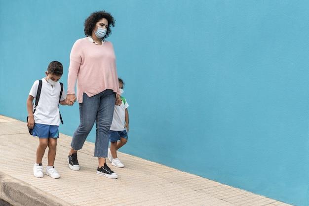 Mutter mit sohn und tochter, die mit sicherheitsmasken zur schule zurückkehren - konzentrieren sie sich auf das gesicht der mutter