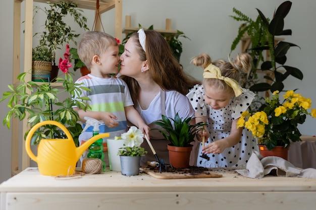 Mutter mit sohn und tochter in fastenpflanze oder verpflanzung von zimmerblumen kleiner helfer bei der hausarbeit