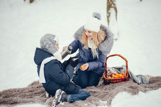 Mutter mit süßen sohn in einem winter oark