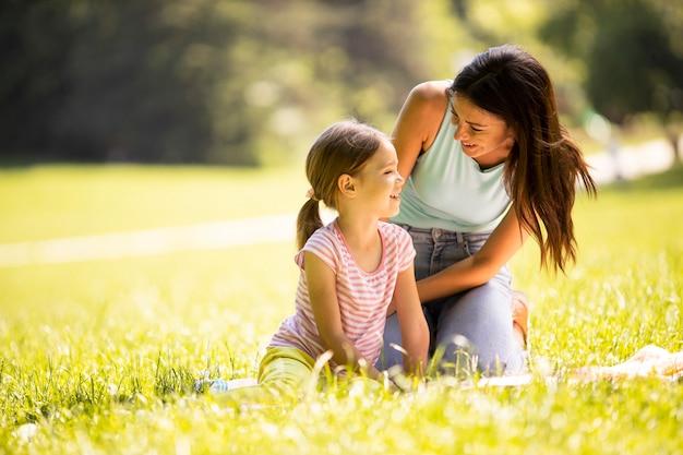 Mutter mit süßer kleiner tochter, die spaß auf dem gras im park hat