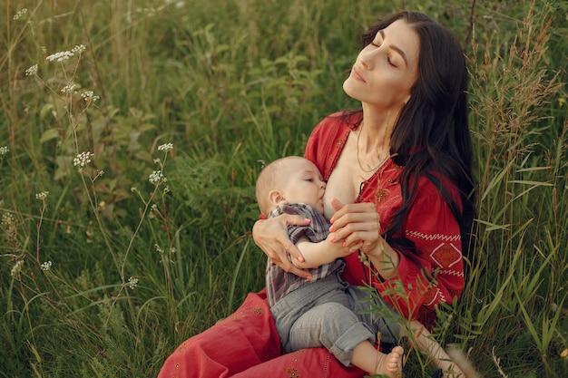 Mutter mit süßer tochter. mutter stillt ihren kleinen sohn. frau in einem roten kleid.