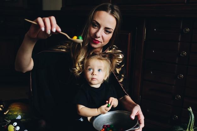 Mutter mit süßigkeiten in einem löffel, während ihre tochter schaut
