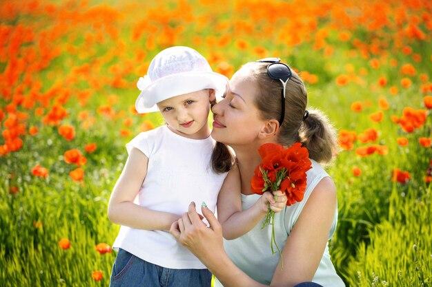 Mutter mit tochter am sonnigen tag der mohnblumen im park