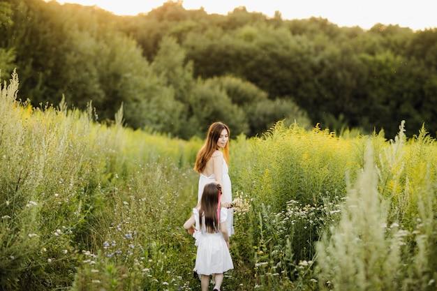 Mutter mit tochter, die entlang einer landstraße geht