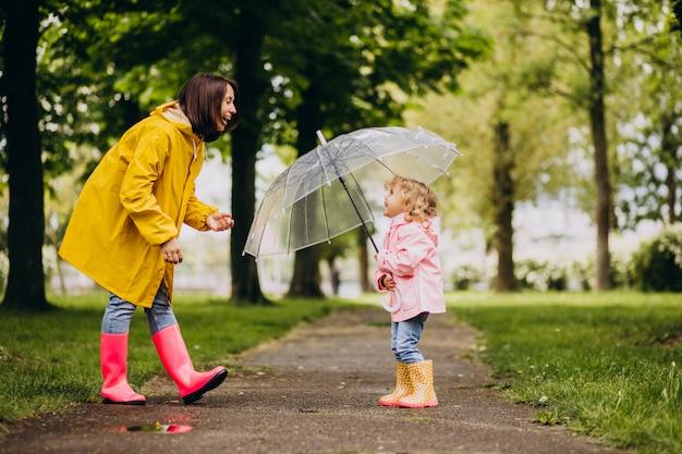 Mutter mit tochter, die im regen unter dem regenschirm geht