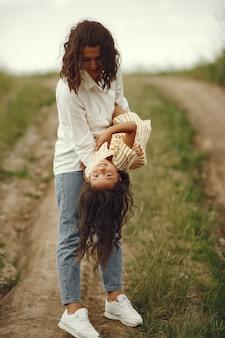 Mutter mit tochter, die in einem sommerfeld spielt