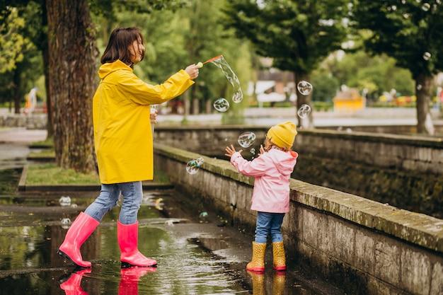 Mutter mit tochter, die spaß im park bei regnerischem wetter hat