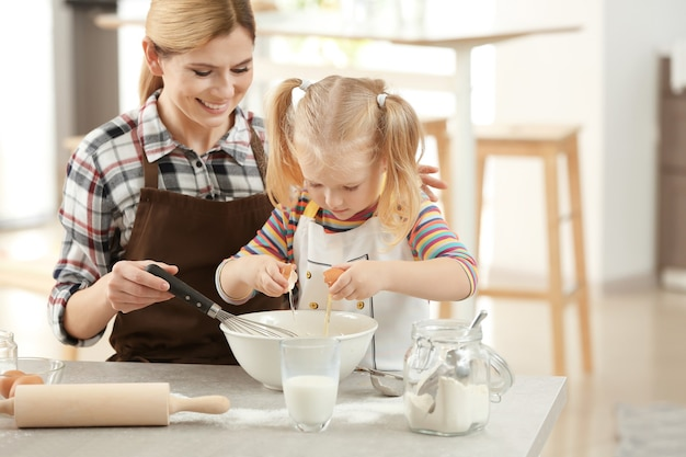 Mutter mit tochter, die teig zusammen in der küche macht