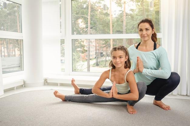Mutter mit tochter, die yogaübung macht