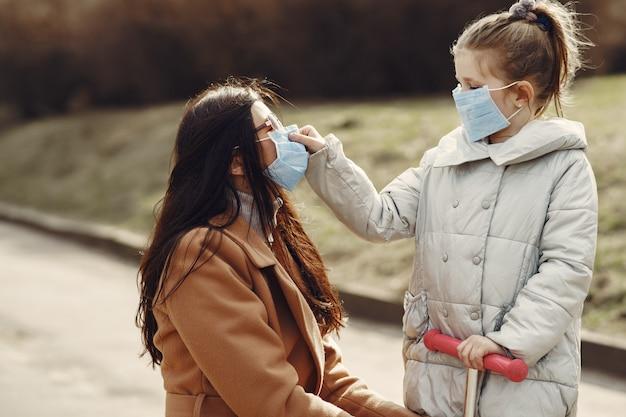 Mutter mit tochter geht in masken nach draußen