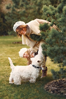 Mutter mit tochter geht mit einem hund spazieren