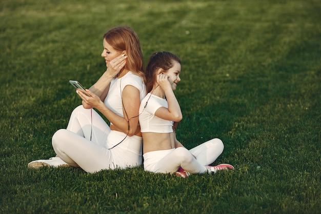 Mutter mit tochter hören musik in einem park