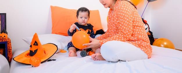 Mutter mit tochter im kostüm zum feiern von halloween zu hause. kind mit mama bei der schlafzimmerdekoration in der herbstsaison.
