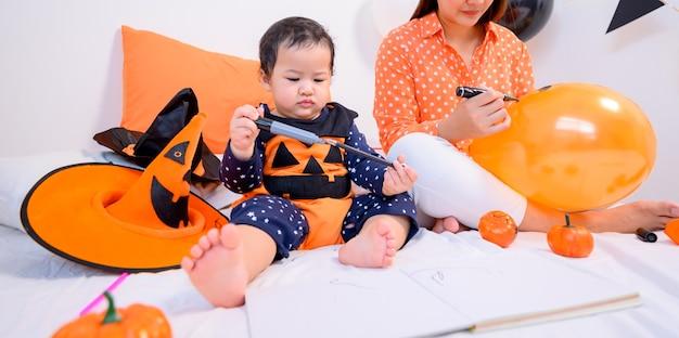 Mutter mit tochter im kostüm zum feiern von halloween zu hause. kind mit mama in der schlafzimmerdekoration