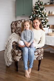 Mutter mit tochter im weihnachtshaushintergrund