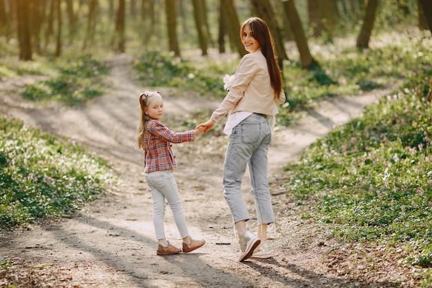 Mutter mit tochter in einem frühlingswald mit hund