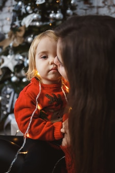 Mutter mit tochter in roten warmen pullovern springen auf das bett. glückliche mutterschaft. warme familiäre beziehungen. weihnachten und silvester interieur. liebe. familienkonzept.