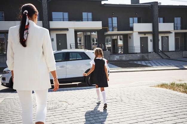 Mutter mit tochter in schuluniform draußen in der nähe von weißem auto.