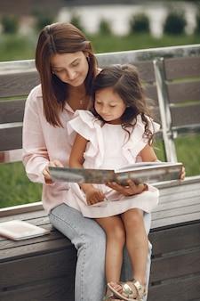 Mutter mit tochter liest ein buch in der stadt