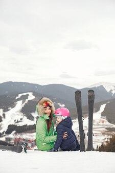 Mutter mit tochter skifahren. menschen in den schneebedeckten bergen.