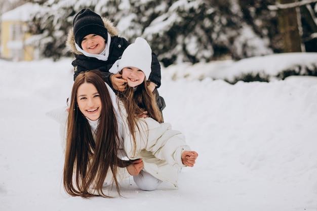 Mutter mit tochter und sohn haben spaß im park voller schnee