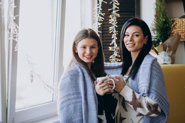 Mutter mit tochter zusammen tee zu trinken, in der küche am fenster
