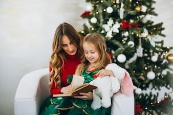 Mutter mit Tochterlesebuch durch Weihnachtsbaum