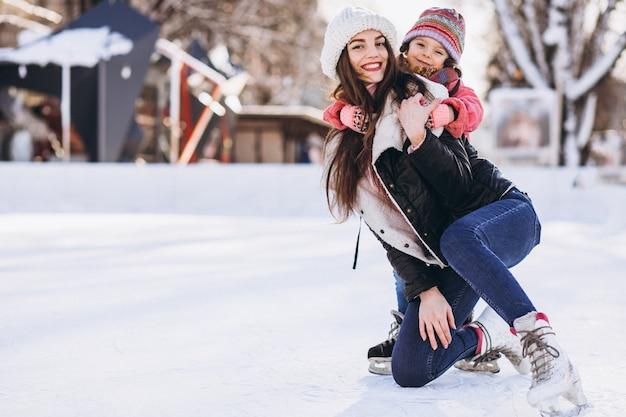 Mutter mit unterrichtendem eislauf der tochter auf einer eisbahn
