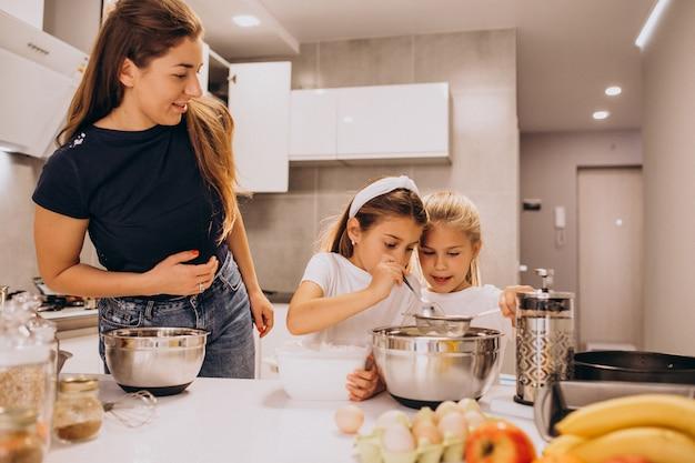 Mutter mit zwei töchtern beim küchenbacken