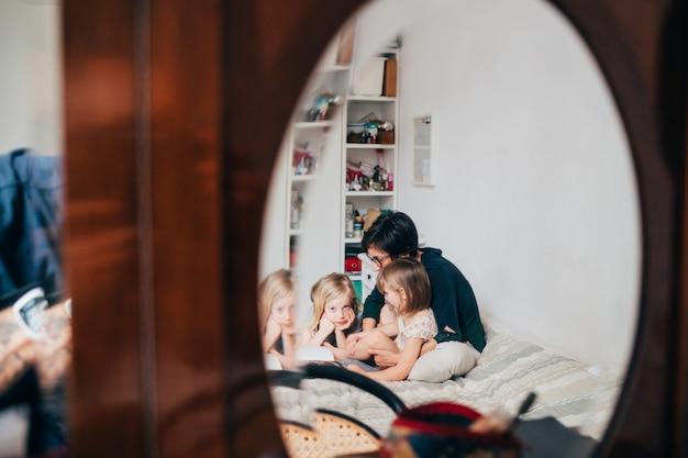 Mutter mit zwei weiblichen kindern, die auf bett lesen, lesen zusammen buch auf einem spiegel