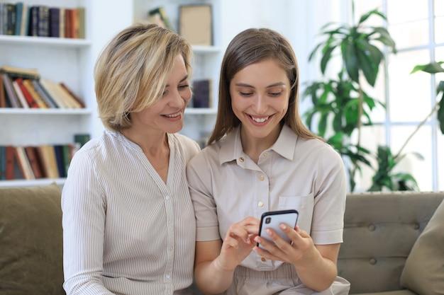 Mutter mittleren alters und erwachsene tochter, die sich umarmen, zusammen telefonieren, videos oder fotos ansehen, auf einer gemütlichen couch zu hause sitzen.