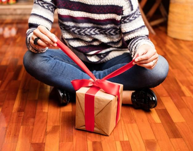 Mutter öffnet ein geschenk auf weihnachten