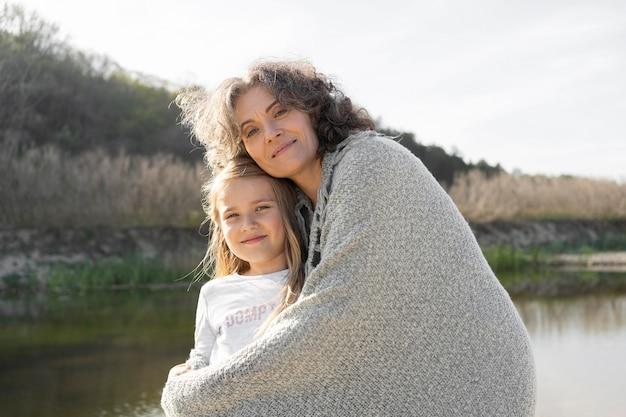 Mutter posiert mit ihrer kleinen tochter im freien