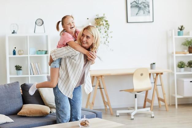 Mutter reitet ihre tochter mit down-syndrom auf dem rücken, während sie im wohnzimmer spielen