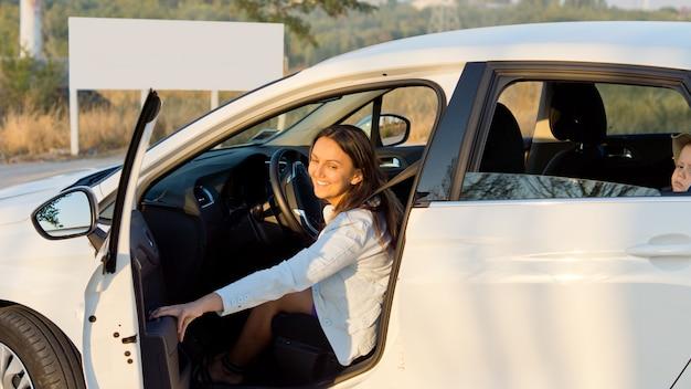 Mutter schließt die autotür, als sie mit ihrem kleinen sohn als beifahrer im fond davonfahren will