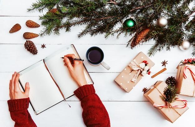 Mutter schreibt in notizbuch und to-do-liste der geschenke für weihnachten und neujahr