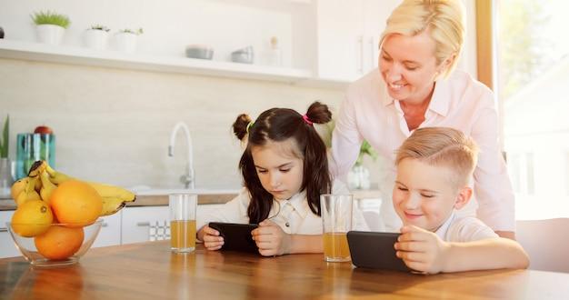 Mutter, schwester und bruder schauen sich gemeinsam ein video auf dem handy an.