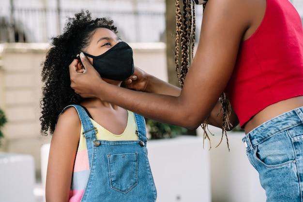 Mutter setzt eine gesichtsmaske auf ihre tochter, während sie draußen auf der straße steht. neues normales lifestyle-konzept.