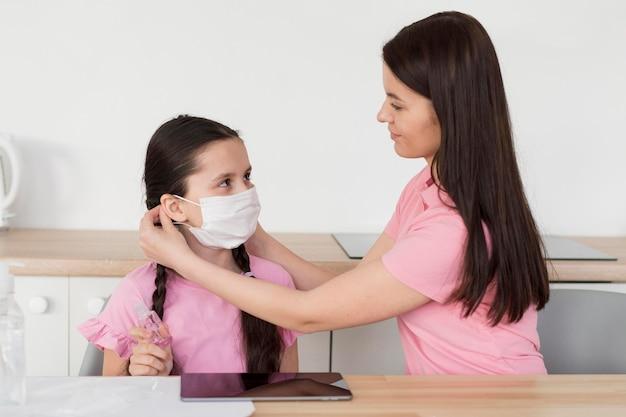 Mutter setzt maske auf kind