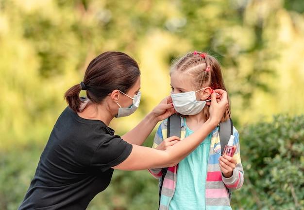 Mutter setzt schutzmaske auf kleine tochter, bevor sie zurück zur schule geht