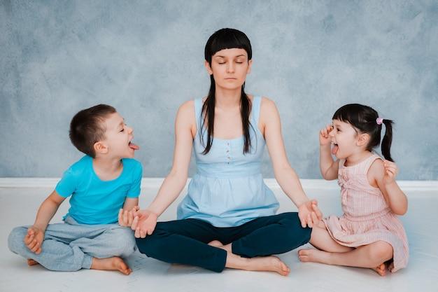 Mutter sitzt auf dem boden und meditiert über die lotus-position. kleine kinder schreien herum und spielen konzentriert und ruhig. mutter meditiert über das balancieren