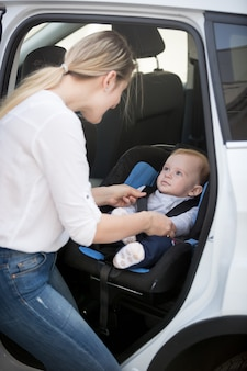 Mutter sitzt ihr baby im autositz