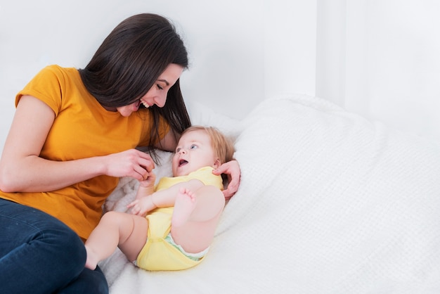 Mutter spielt mit baby im bett