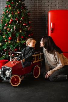 Mutter spielt mit baby neben weihnachtsbaum