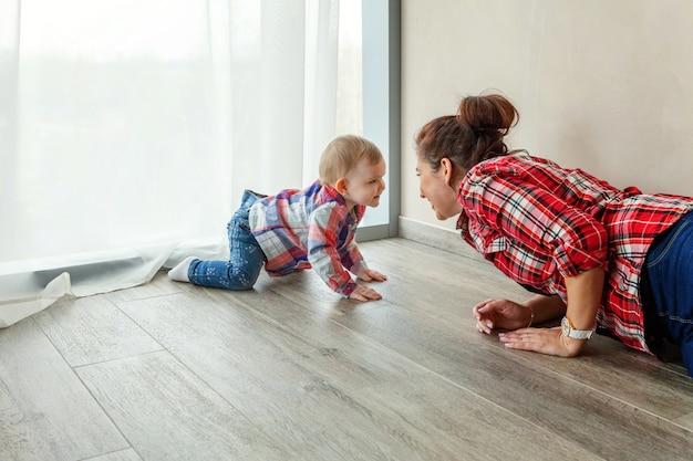 Mutter spielt mit ihrer tochter. frau und kleines mädchen entspannen sich zu hause