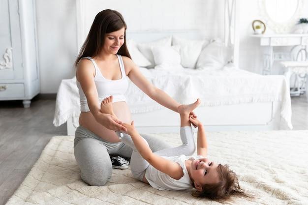 Mutter spielt mit ihrer tochter im schlafzimmer