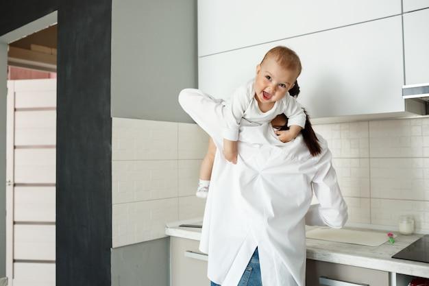 Mutter spielt mit kleinem baby in der küche