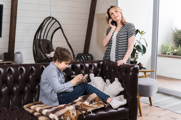 Mutter spricht am telefon, während sohn hausaufgaben macht